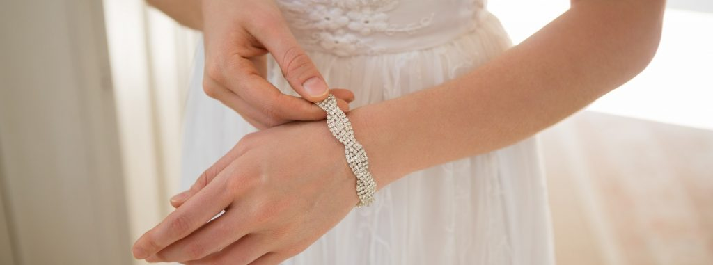Midsection of bride wearing bracelet at home